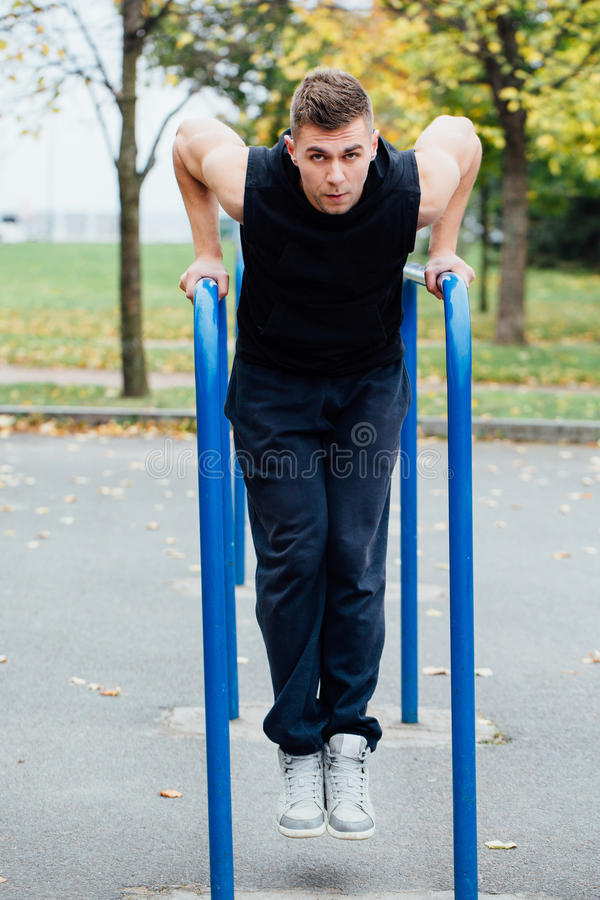被聚焦的肌肉年轻人画象黑锻炼的给做在双杠的垂度穿衣 图库摄影