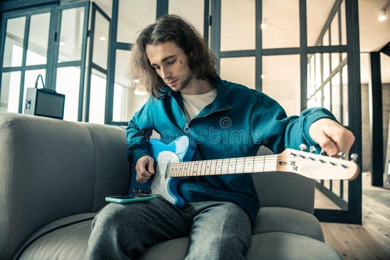 被聚焦的英俊的年轻人坐灰色长沙发和调整的吉他 免版税库存图片