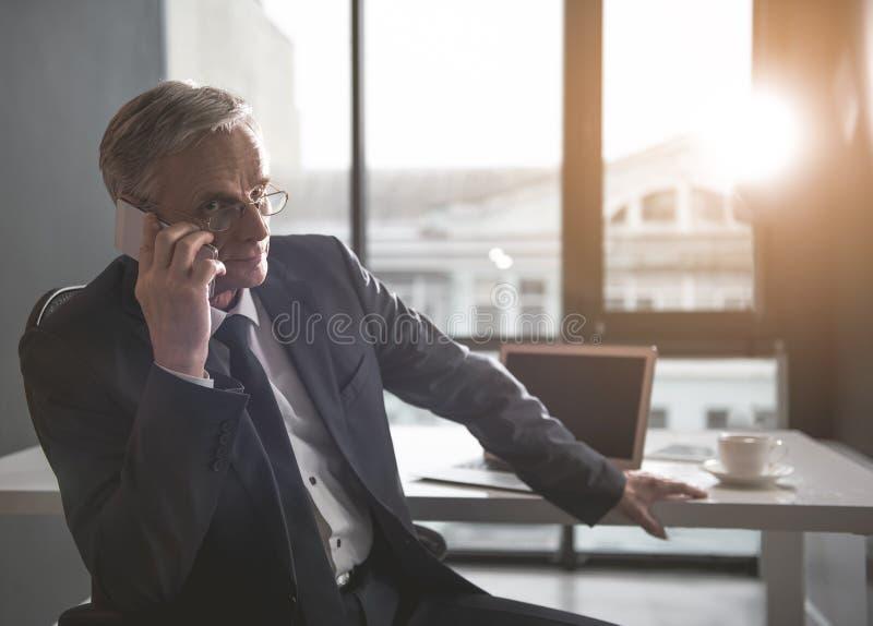 被聚焦的资深商人讲话由电话 库存图片