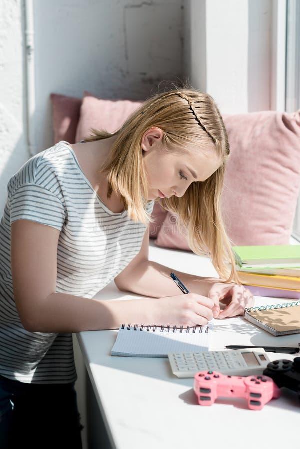 被聚焦的青少年的学生女孩侧视图  免版税库存图片