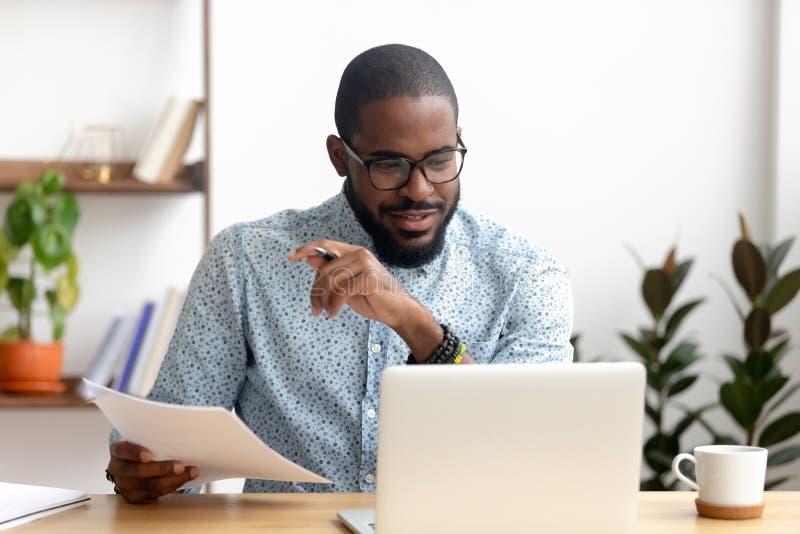 被聚焦的非裔美国人的商人与膝上型计算机文件一起使用在办公室 库存图片
