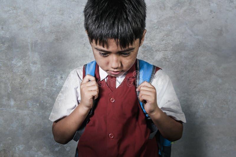 被胁迫的年轻人虐待了一致运载的书包哀伤沮丧的男小学生在感觉一个孤独和被注重的孩子受害者的黑板 免版税库存图片