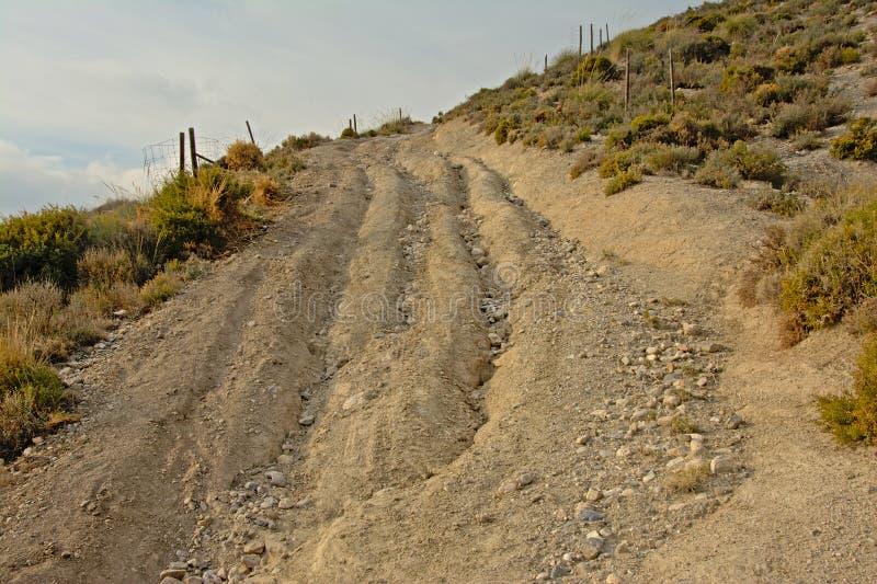被腐蚀的土路通过与软的云彩的内华达山山晴天 库存图片