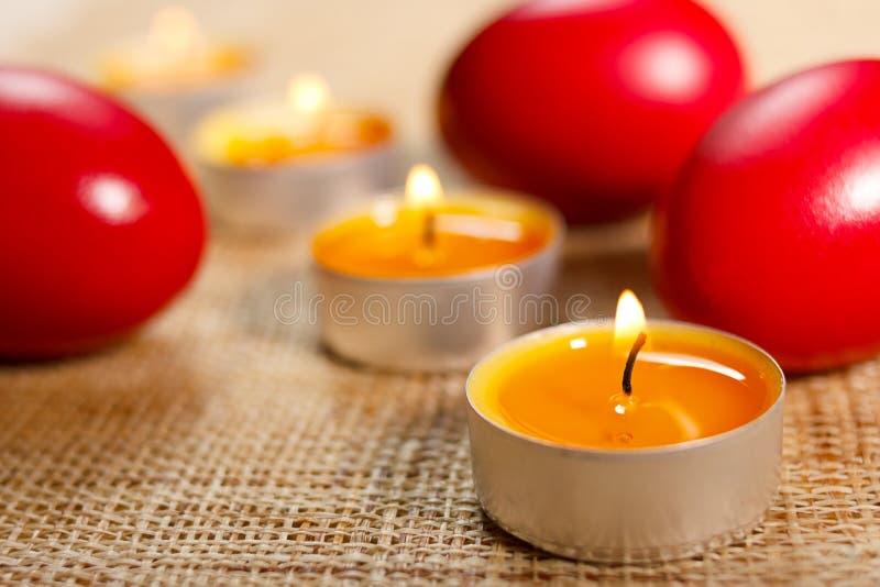 被舍入的蜡烛被安置在三个红色鸡蛋之间 库存照片