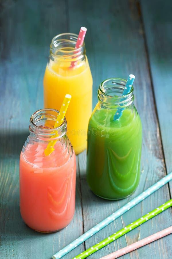 被装瓶的桃红色,黄色和绿色饮料 五颜六色的汁液 夏天饮料 库存照片