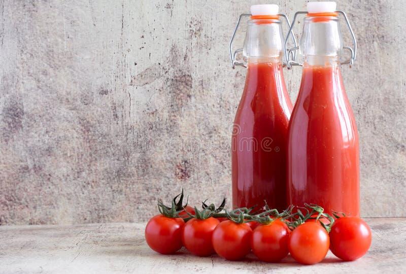 被装瓶的西红柿汁和新鲜的蕃茄在桌上 免版税库存照片