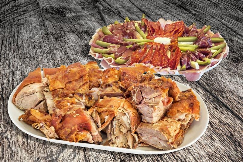 被装饰的开胃菜美味在老被风化的破裂的松林庭院桌上设置的盘和满盘新烤猪肉肉切片 图库摄影