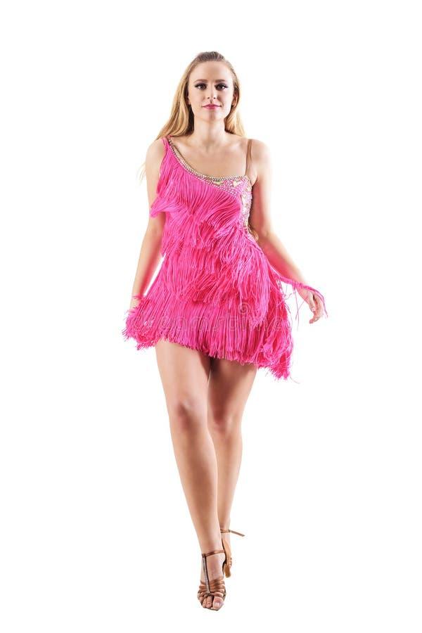 被装饰的礼服的走和看照相机的白肤金发的妇女正面图  免版税库存图片