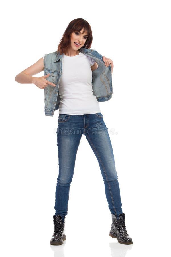 被解扣的牛仔裤夹克的妇女指向她自己 免版税库存照片