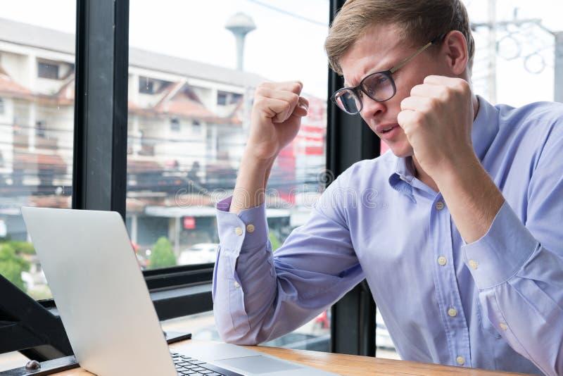 被触怒的商人看看膝上型计算机 举行他的恼怒的年轻人 库存照片