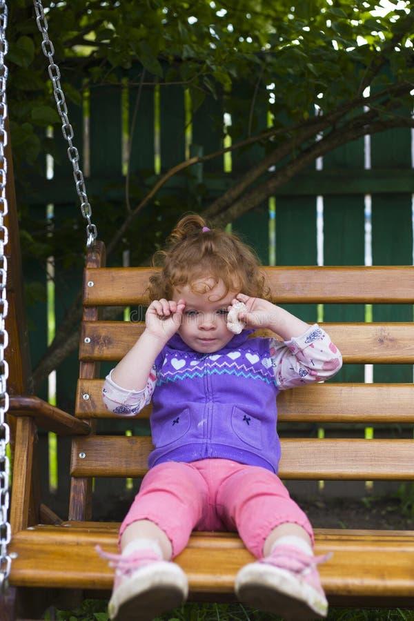 被触犯的女孩坐一条长凳用曲奇饼 图库摄影