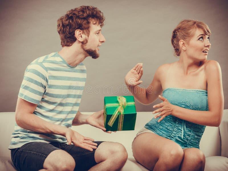 给被触犯的妇女礼物盒的年轻人 免版税库存照片