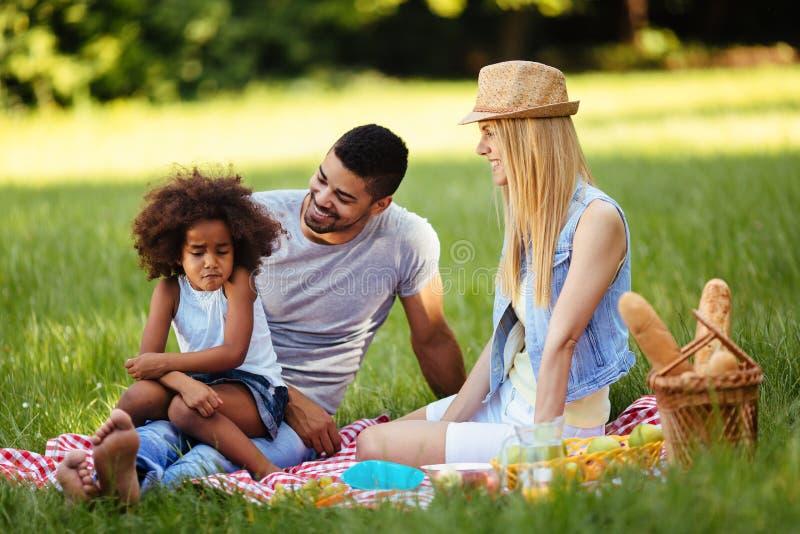被触犯的小女孩与父母坐野餐 库存照片