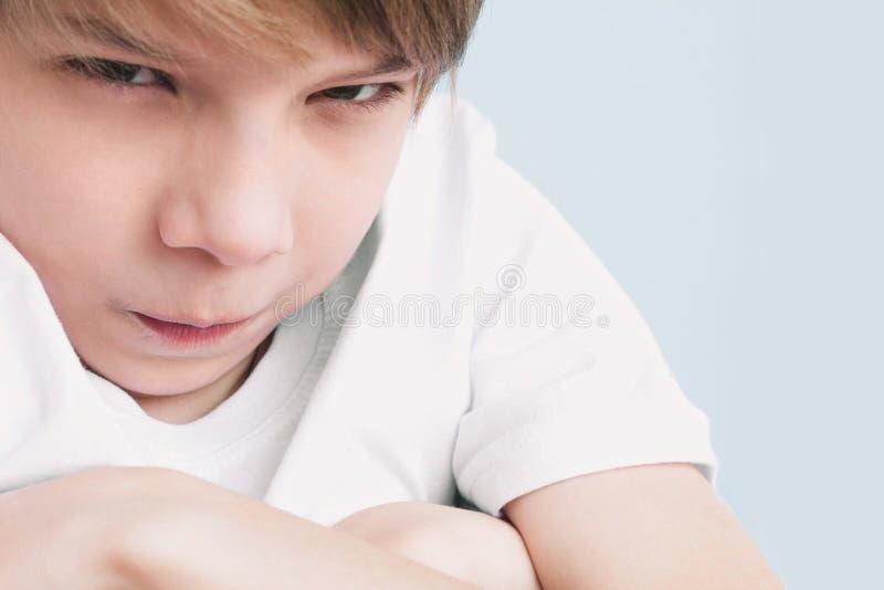被触犯的男孩交叉他的双臂并且愤怒看照相机 免版税库存照片