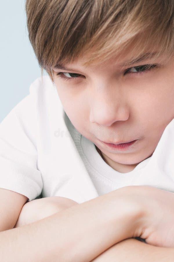 被触犯的男孩交叉他的双臂并且愤怒看照相机 免版税图库摄影