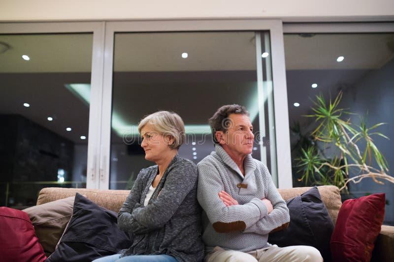 被触犯的资深夫妇坐有横渡的胳膊的一个长沙发 免版税库存照片