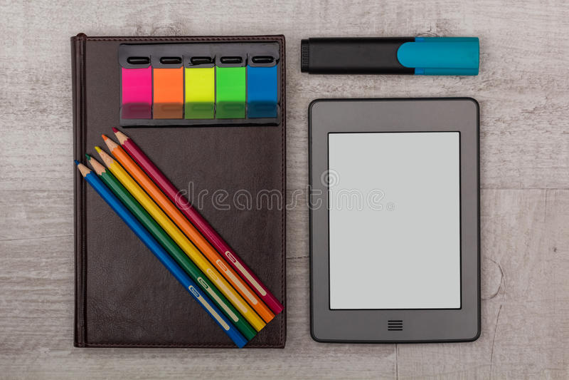 被设置的事务:日志、一本e书与蜡笔和标志 库存图片