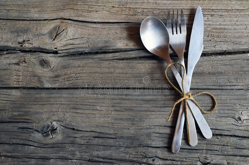 被设置的利器:叉子、匙子和刀子在土气木桌上 在老木背景的利器 能使用当背景菜单为restau 库存图片