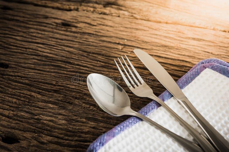 被设置的利器:葡萄酒刀子、叉子和匙子在白色木backg 库存图片