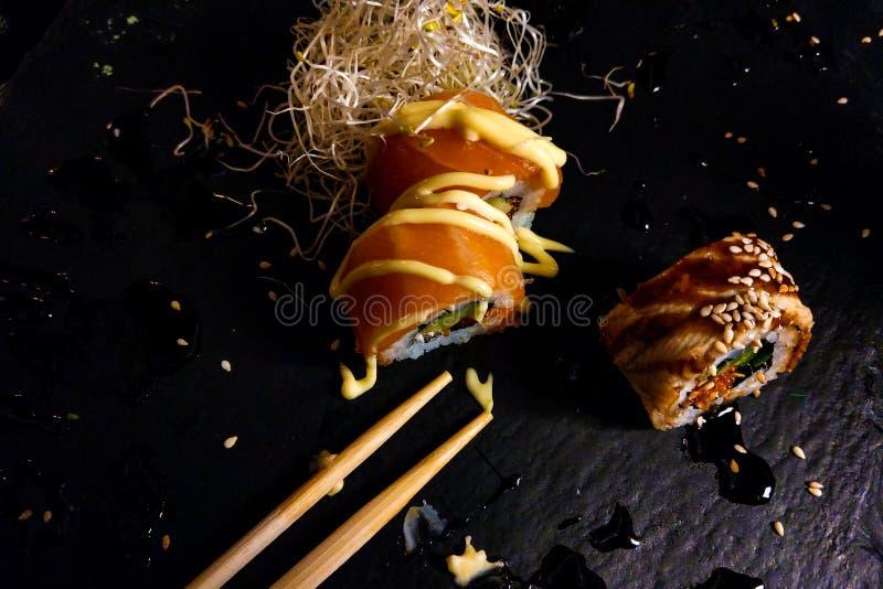 被设置的寿司卷在黑暗的背景的黑石板岩服务 库存图片