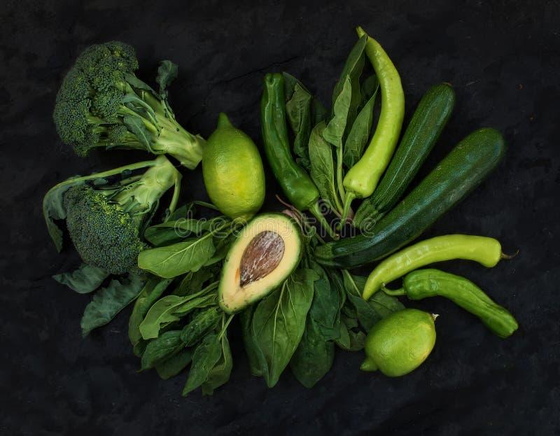 被设置的未加工的绿色菜 硬花甘蓝、鲕梨、胡椒、菠菜、zuccini和石灰在黑暗的石背景 免版税图库摄影