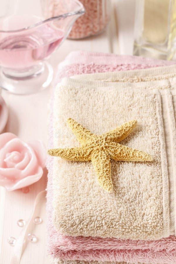 被设置的桃红色温泉:液体皂、精油、毛巾和海盐 免版税库存照片