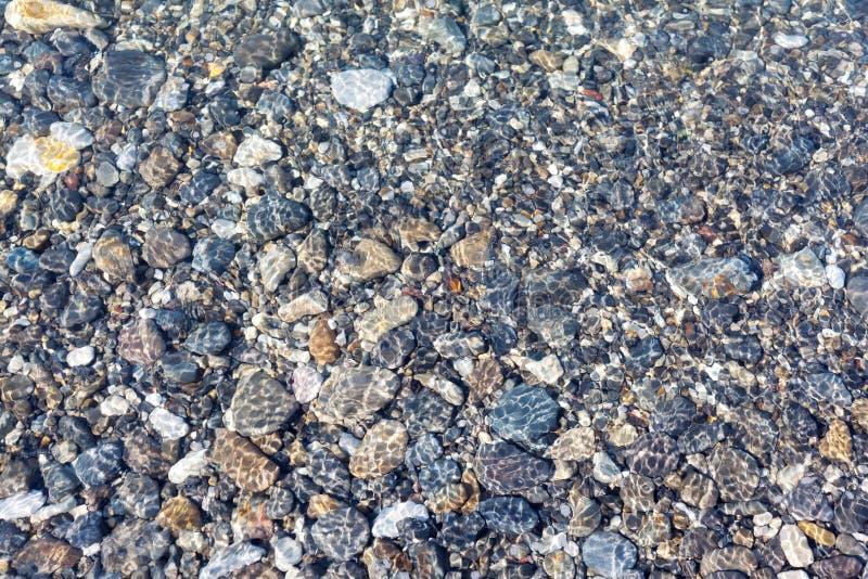 被设置的自然:在水背景下的海小卵石 免版税库存图片