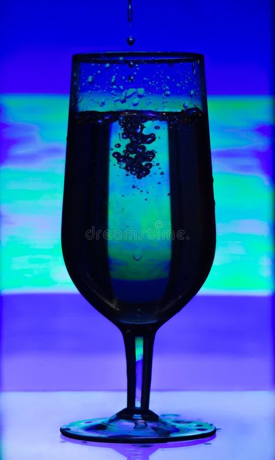 被设色的杯香槟与飞溅液体在摘要被弄脏的背景 免版税图库摄影