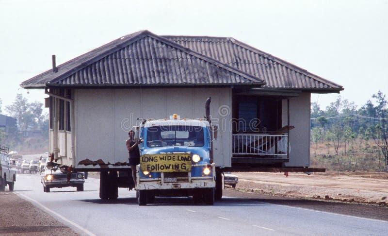 被调迁在一辆低装载者卡车背面的老房子 库存图片