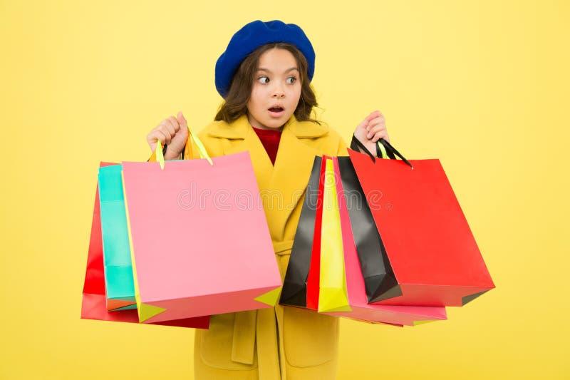 被购物占据心思 在黄色背景的女孩逗人喜爱的孩子举行购物带来 中间季节销售 有优惠券的商店 库存照片