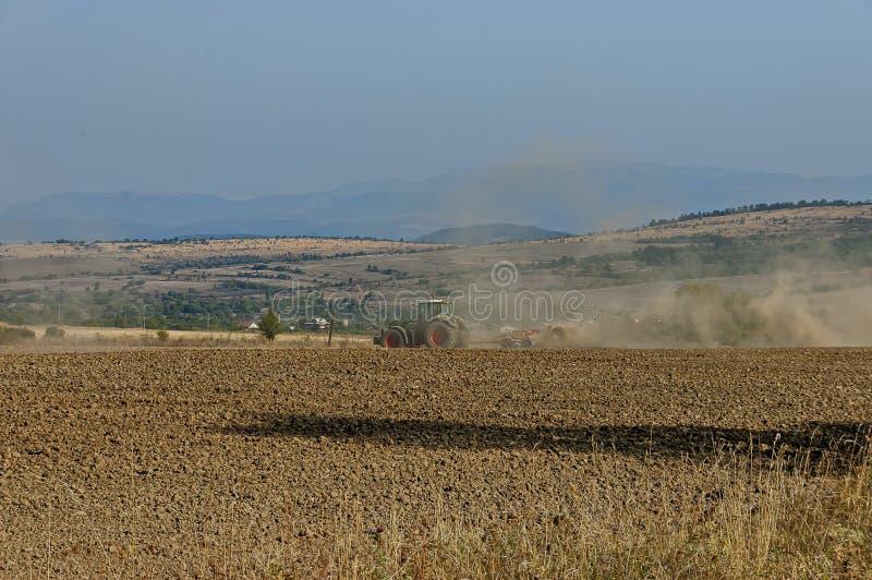 被转动的拖拉机的农夫土地为播种耕地做准备, Bailovo村庄, Sredna gora山 库存照片
