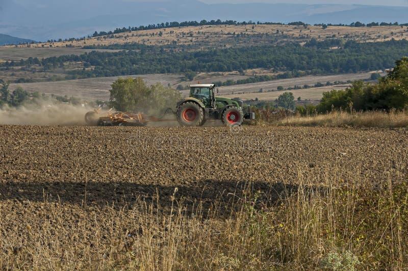 被转动的拖拉机的农夫土地为播种耕地做准备, Bailovo村庄, Sredna gora山 免版税库存照片