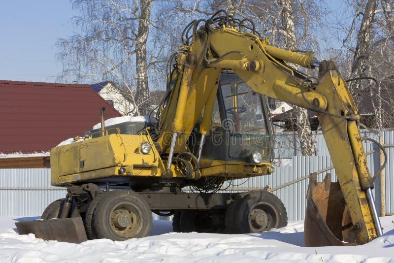 被转动的挖掘机站立在露天下在围场在冬天 图库摄影