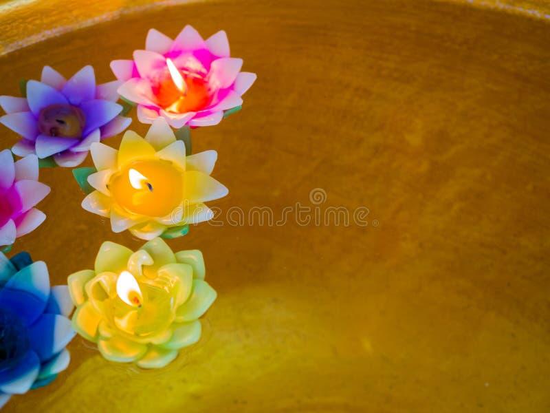 被过滤的颜色:在漂浮在水、寺庙和留心背景概念的花五颜六色的持有人的蜡烛 库存照片