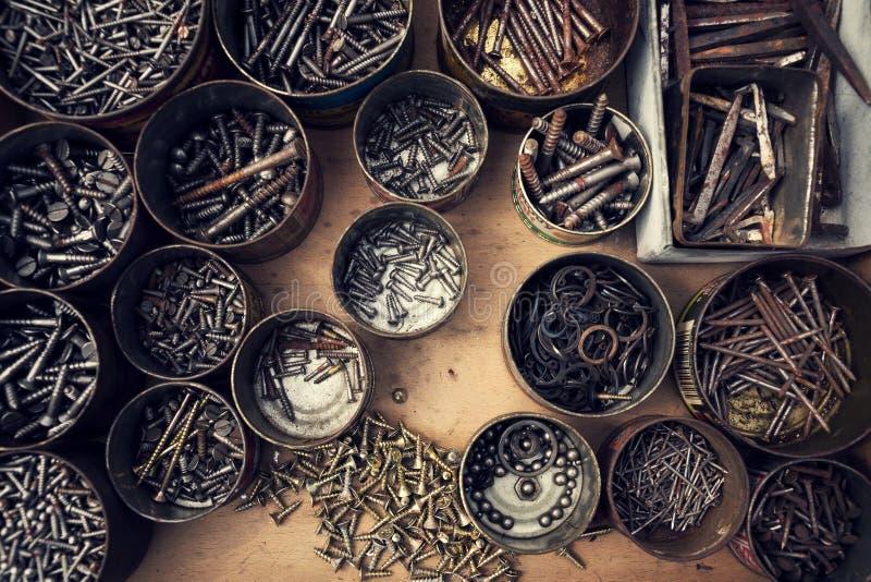 被过滤的螺丝和螺栓在锡罐在木背景 免版税库存图片