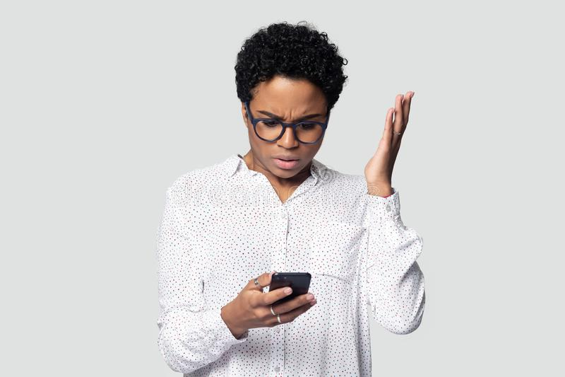 被迷惑的两种人种的妇女有故障问题使用手机 免版税库存照片