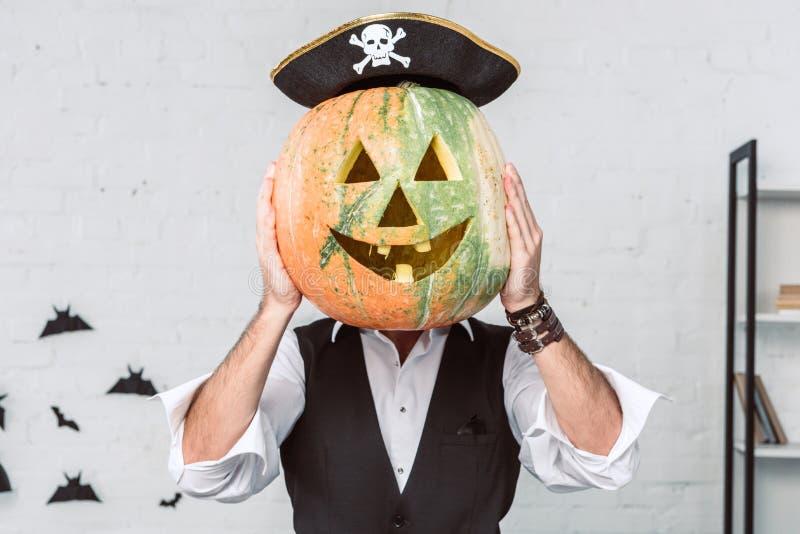 被遮暗的观点的海盗服装覆盖物面孔的人用南瓜万圣节 图库摄影