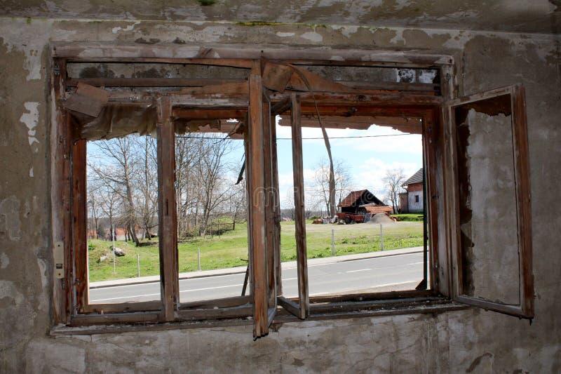被铺的路和房子看法从里边被放弃的房子通过与在崩裂登上的残破的窗架的被毁坏的窗口 库存图片