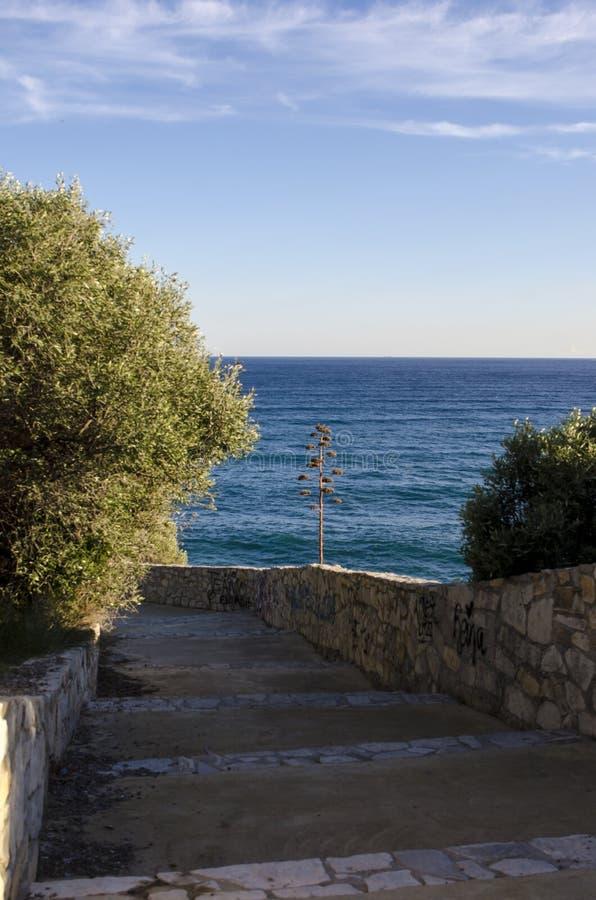 被铺的道路向海滩的蓝色清楚的mediteranean海在晴天 免版税图库摄影