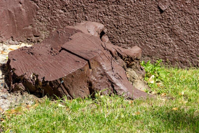 被锯的木头老木树桩绘与在一个石墙的背景的棕色油漆 创造性的风景设计的例子 库存图片