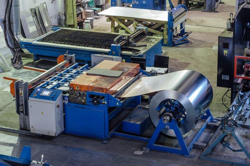 被镀锌的钢片卷制造的金属管子和管的在工厂 库存照片