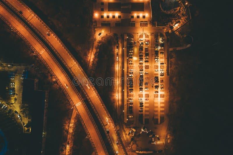 被阐明的城市汽车停车处空中顶视图与车的在机动车路附近的晚上有交通的 库存图片