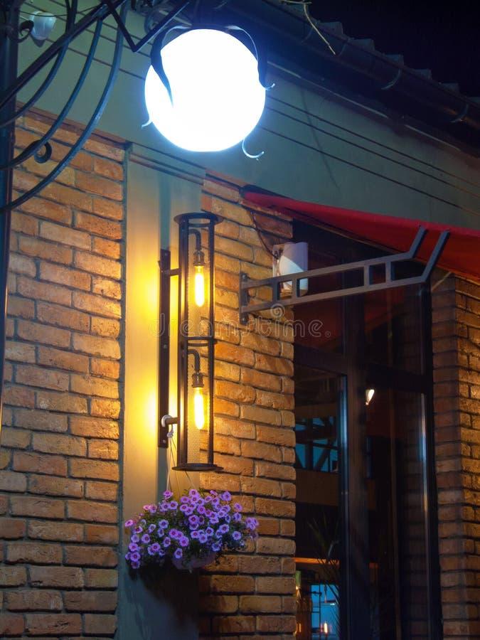 被阐明的灯'月亮'砖墙花勿忘草夜光,度假区的装饰设计 库存图片