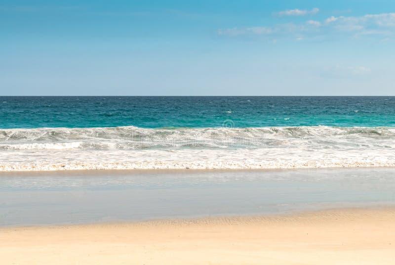 被隔离的海滩热带海岛,有风平浪静波浪、天空蔚蓝和可见地平线的 梦想目的地假日/假期 图库摄影