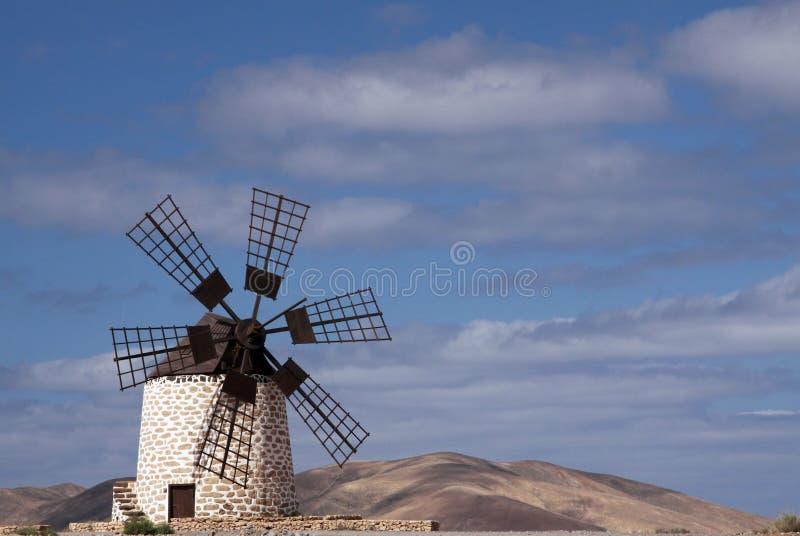 被隔绝的传统风车Molino在La奥利维亚附近的de Tefia在反对天空蔚蓝的干燥干旱的多小山风景与积云, 免版税库存照片