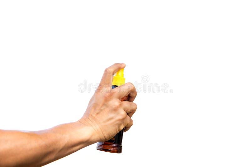 被隔绝的手喷洒的遮光剂保护油 免版税图库摄影