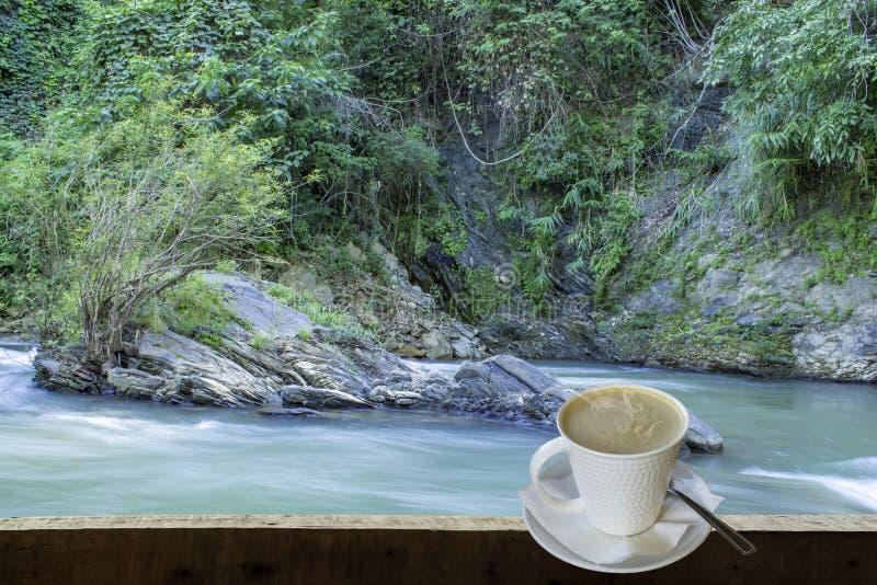 被隔绝的热的咖啡投入了白色玻璃与一个偶然断裂的为 免版税库存照片