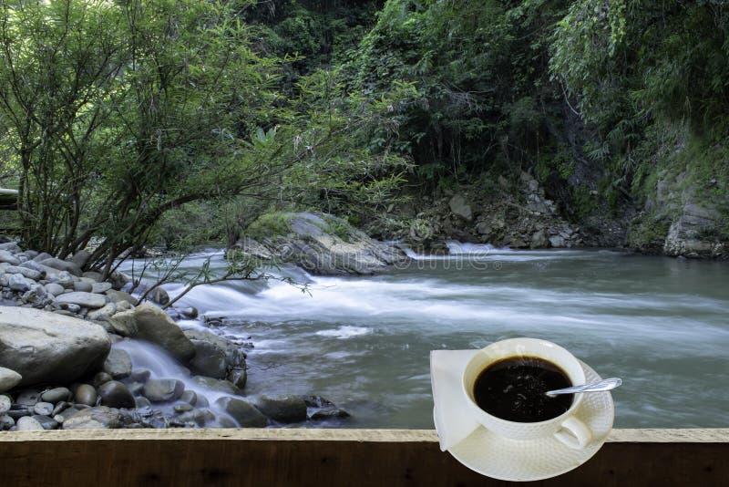 被隔绝的热的咖啡投入了白色玻璃与一个偶然断裂的为 库存图片