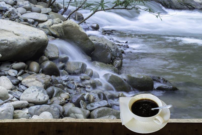 被隔绝的热的咖啡投入了白色玻璃与一个偶然断裂的为 免版税图库摄影