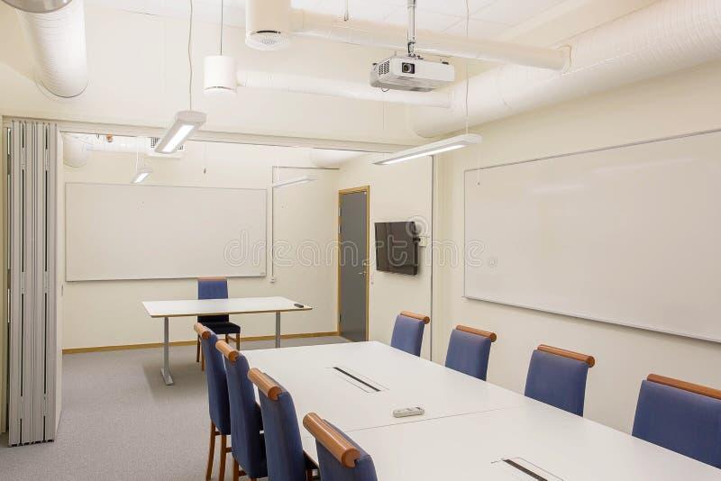 被隔绝的现代会议/会议室 白色办公室桌和蓝色椅子 到达天空的企业概念金黄回归键所有权 现代办公室样式 免版税库存照片